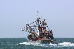 A fishing boat is at sea fishing. Royalty Free Stock Images