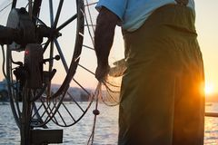Fishing boat in a sea. Hands with net of an old fisherman Stock Photos