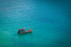 Fishing boat in the sea. A lone fishing boat in the blue sea ripples royalty free stock photo