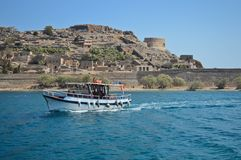 Fishing boat on the sea with Spinalonga island and fortress in the background. Historical Spinalonga Fortress nearby Crete Island, Greece with a fishing boat Royalty Free Stock Images