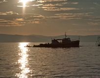 Fishing boat in sea at sunset royalty free stock photography