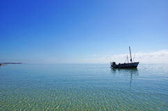 Fishing boat in shallow waters of the pacific ocean. Fishing boat in shallow, blue waters of the pacific ocean in south-east Africa royalty free stock images