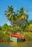 Fishing boat on the shore of a tropical river. Royalty Free Stock Image