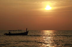 Fishing boat silhouette at sunset. Fishing boat silhouetted against the setting sun in a tropical location Stock Photos