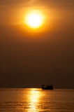 Fishing boat silhouetted with the sun Royalty Free Stock Image