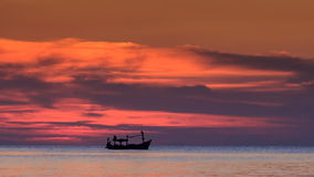 Fishing Boat at Skyline Red Clouds in Dark Sky after Sunset stock footage