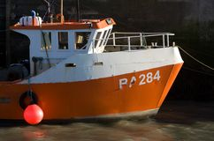 Fishing boat. A small orange hulled fishing boat alongside the harbour wall at Padstow, Cornwall, UK stock image