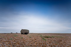 A solitary fishing boat on a deserted pebble beach Stock Images
