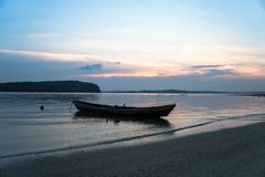 Fishing boat in Songkhla Lake At sunset. Silhouettes on sea water background stock images