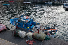 The fishing boat. Sorrento, Italy - October 5, 2012: Fisherman unwinds the net after fishing royalty free stock photos