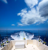 Fishing boat stern deck with trolling fishing rods and reels. In blue ocean sea Stock Photography
