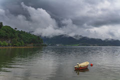 Fishing boat on a still lake and  mountains in background. Fishing boat on a still lake and high mountains in background Stock Photos