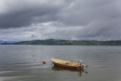 Fishing boat on a still lake and  mountains in background. Royalty Free Stock Photo