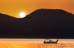Fishing Boat and The Sun Stock Photo