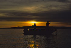 Fishing boat in Sunrise. Two fisherman in a boat at sunrise Royalty Free Stock Images
