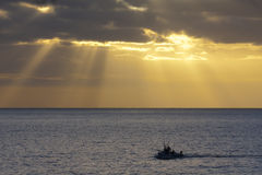 Fishing boat at sunset. Fishing boat returning to the harbour in the azores at sunset royalty free stock images