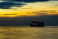 Fishing boat at sunset. Back lit traler on the ocean at sunset Royalty Free Stock Image