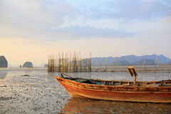 Fishing boat at sunset. Fishing boat stranded on mud at low tide, Ao Thalane, Krabi province, Thailand Stock Photo