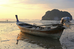 Fishing boat at sunset. Fishing boat stranded on mud at low tide, Ao Thalane, Krabi province, Thailand Royalty Free Stock Image