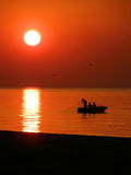 Fishing boat at sunset. Three fisher-mans in the fishing boat near the beach at sunset Stock Image