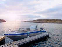 Fishing boat at sunset calm water. A motorboat for sport fishing tied to a wooden pier Royalty Free Stock Photo