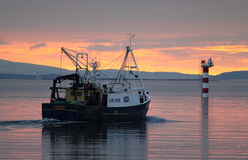 Fishing boat at sunset, Oban Bay, Scotland. Small fishing boat leaving Oban Bay at sunset heading into the Firth of Lorn, Argyll and Bute, Scotland. In the Royalty Free Stock Photography