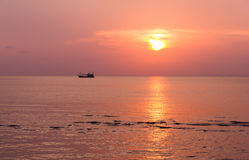 Fishing boat at sunset in the sea Stock Image