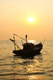 Fishing boat at sunset Stock Photos