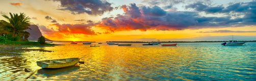 Fishing boat at sunset time. Le Morn Brabant on background. Panorama landscape. Fishing boat at sunset time. Le Morn Brabant on background. Mauritius. Panorama stock photos