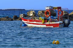 Fishing boat surrounded by rocks Stock Photos