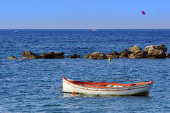 Fishing boat surrounded by rocks Royalty Free Stock Photos