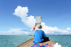 Fishing boat thailand. A boy in fishing boat go to the sea at blue sky of the day stock photos