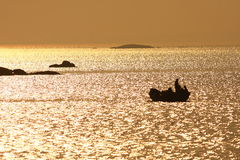 Fishing boat in thegolden sea Stock Photo