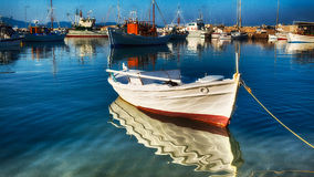 Fishing boat. Tied fishing boat casting an early sunset  reflection on the water Royalty Free Stock Photo