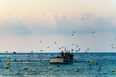 Fishing boat about to go out to sea at dawn, seagulls and clouds. royalty free stock images