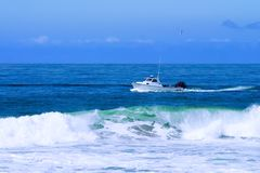 Fishing Boat Trawling For Fish And Checking Lobster Traps. In Ocean Waves Royalty Free Stock Photography