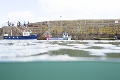 Fishing boat trip from Mousehole Harbour. A few fishing boats in Mousehole Harbour. One of which is picking up tourists and taking them on a fishing trip around Royalty Free Stock Images