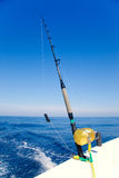 Fishing boat trolling in ocean with golden reel Stock Image