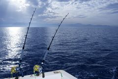 Fishing boat trolling with two rods and reels. On blue ocean Stock Image