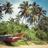 Fishing boat on a tropical beach with palm trees in the backgrou Royalty Free Stock Photography