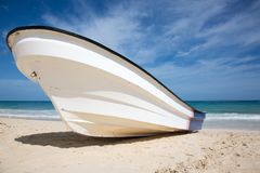 Fishing boat on a tropical beach at a sunny day. A fishing boat on a tropical beach at a sunny day royalty free stock image