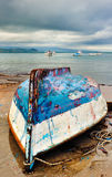 Fishing boat upside down. Picture from a fishing village showing an upside down and heavily weathered fishing boat stranded on the beach. Room for text on top Stock Images