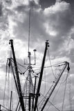 Fishing Boat Vessel Fleet Mast and Outrigger Booms. Menacing storm clouds sky over docked and lined up fishing boat vessel fleet silhouetted masts and trawling Royalty Free Stock Images