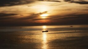 Fishing Boat in Water at Sunset Stock Photo