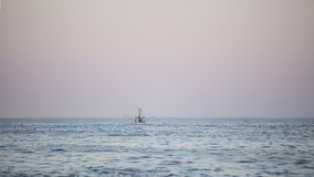 Fishing boat on water at sunset Stock Images