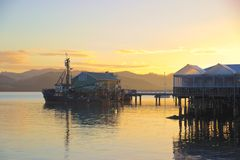 Fishing boat at wharf, fish shop, sunrise, Mangonui, New Zealand Royalty Free Stock Images