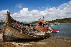 Fishing boat wrecked into a rocky river bank Royalty Free Stock Images