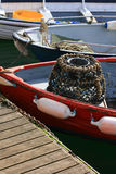 Fishing boats. A Lobster and Crab pot at the front of a small red fishing boat located at Salcombe Bay, Devon England UK Royalty Free Stock Images