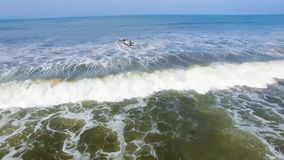 Fishing boats against the waves of the ocean. Fishermen`s boats are buffeted by sea waves as they head out into the open seas to catch fish stock video footage