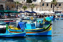 Fishing boats along the waterfront, Marsaxlokk. Traditional Maltese Dghajsa fishing boats in the harbour with waterfront buildings and restaurants to the rear Stock Photo